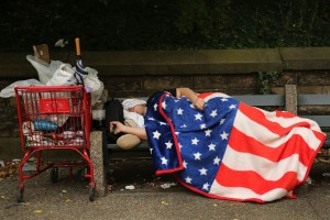 NEW YORK, NY - SEPTEMBER 10: A homeless man sleeps under an American Flag blanket on a park bench on September 10, 2013 in the Brooklyn borough of New York City. As of June 2013, there were an all-time record of 50,900 homeless people, including 12,100 homeless families with 21,300 homeless children homeless in New York City. (Photo by Spencer Platt/Getty Images) *** BESTPIX ***