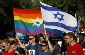 Participants hold flags during the gay pride parade in Jerusalem July 29, 2010. This year's parade marks the one-year anniversary of a shooting attack in a gay and lesbian youth center in Tel Aviv, in which two people were killed and 13 were injured. REUTERS/Ronen Zvulun (JERUSALEM - Tags: POLITICS SOCIETY) - RTR2GURG